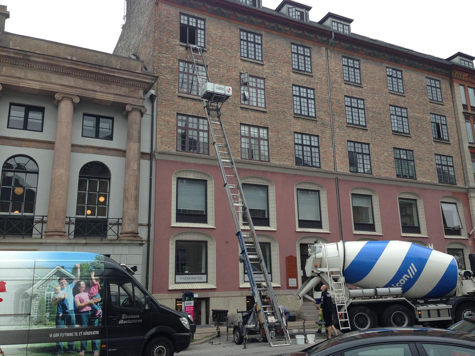Her kan du se en kunde har bestilt en flyttelift til at transportere cement op til 4 sal gennem vinduet. Dette gør at cementen ikke når at tørre inde den bliver brugt.