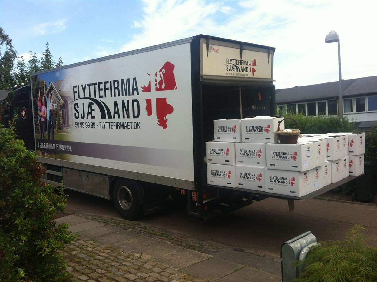 Her ses vores lastbil med fyldt lad med flyttekasser, klar til at blive båret ind hos vores kunde.