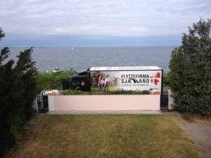 Lastbil holder ude ved havet, lige uden foran kundes hus.