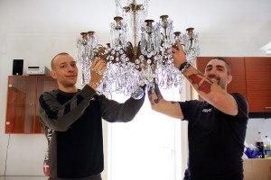 Her kan du se 2 flyttemænd igang med at nedtage en lysekrone under nedpakning af kæmpe hus flytning.