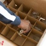 Her ses nedpakning af glas i en flyttekasse