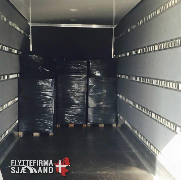 Her ses pallerne pakket ned og filmet og sat på en lastbil.