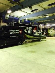 Her ses flyttebil med båd til opbevaring.