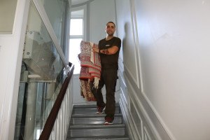 Flyttemand på vej ned af trappe på Østerbro med tæppe.