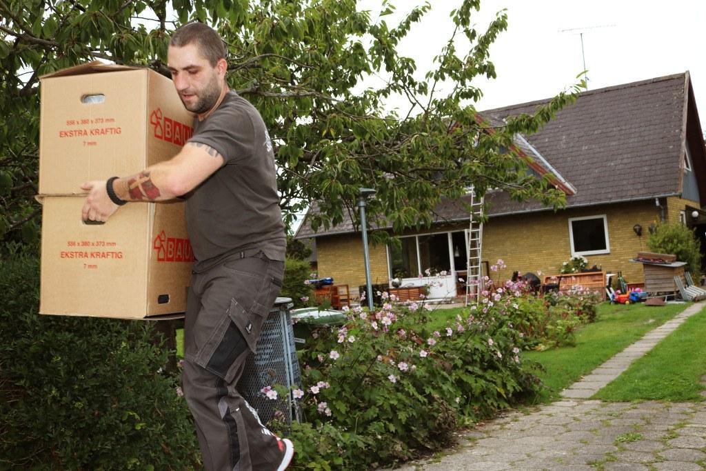 Flyttemand igang med at bære flyttekasser på gigaspace lastbil