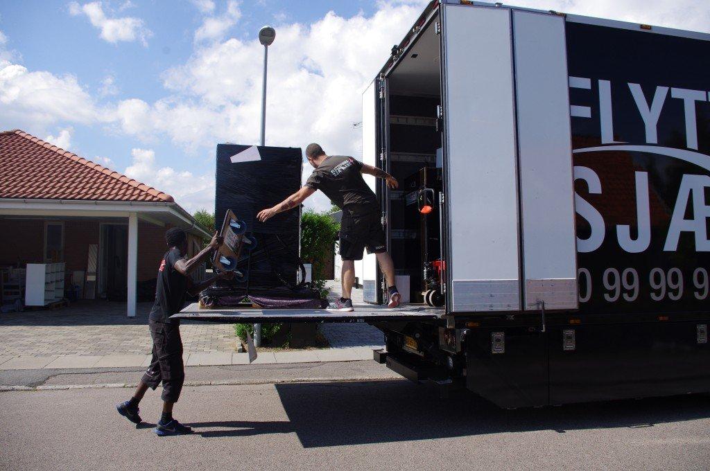 Her ses 2 flyttemænd der samarbejder på en flytning