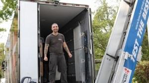 Her ses glad flyttemand på flyttebil ved siden af en flyttelift.